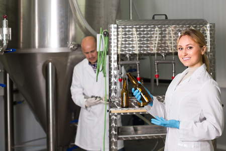 bottling: Friendly smiling young woman bottling beer in glass bottles on modern brewery Stock Photo