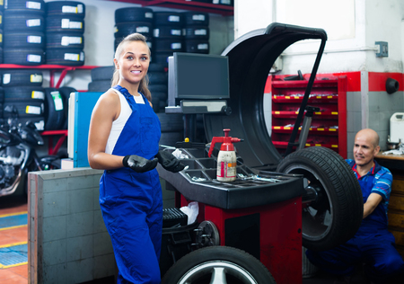 wheel balancing: Young american female technician standing with wheel balancing machinery at auto workshop