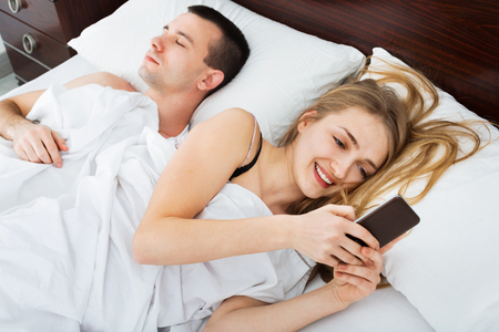adultery: Beautiful smiling young  wife texting with lover on smartphone while husband is sleeping