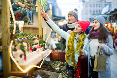 cheerful family of three at Christmas market outdoors