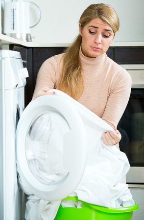 Tired blonde girl with dirty white shirt near washing machine