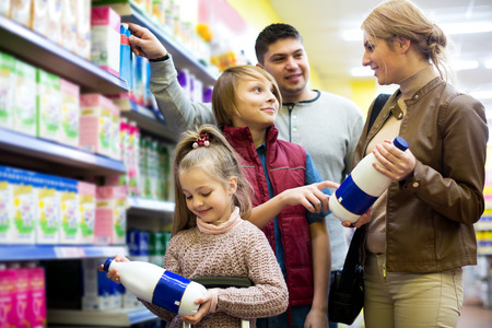 skim: Attractive family of customers with children purchasing milk in shop
