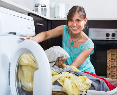 householder: Smiling young woman with basket of linen near washing machine Stock Photo
