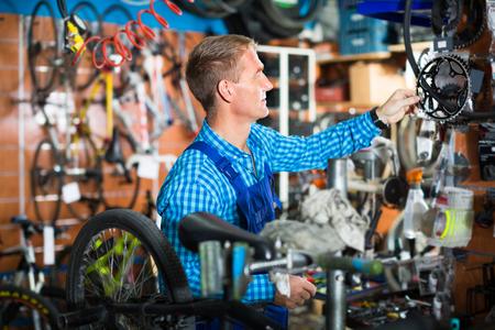 smiling man seller in uniform repairing bicycle in sport hypermarket