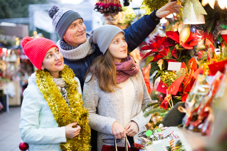 friendly parents with teenage girl at counter with Poinsettia and  floral decorations at the fair Stock Photo