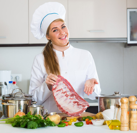 Young woman cooking meat for dinner in home interior
