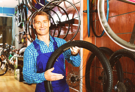 smiling man seller wearing uniform standing with bike wheel in hand in store Stock Photo