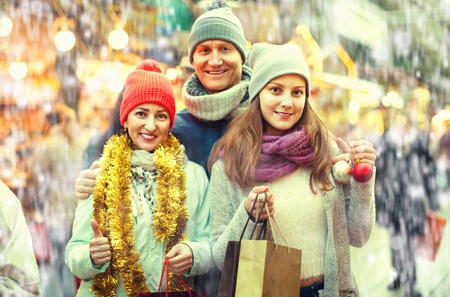 Happy cheerful family of three posing at Christmas market