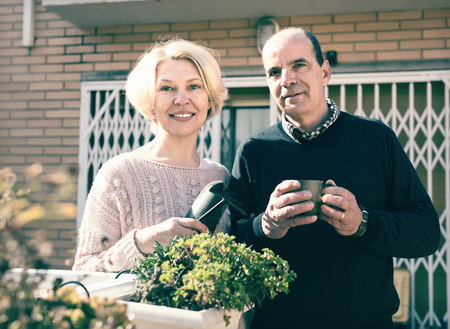 Senior couple on a terrace near their home. Mature woman is holding gardening accesories and man is drinking tea from a cup