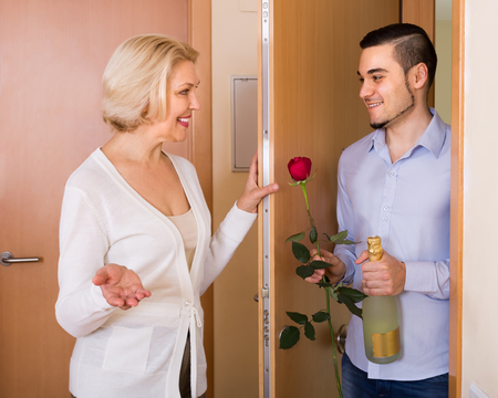 Smiling elderly woman meeting young handsome guy with flowers and wine in hands at doorway Stock fotó
