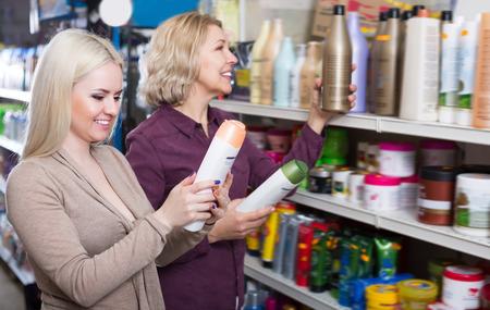 Ordinary women chooses shampoo in cosmetic store Stock Photo
