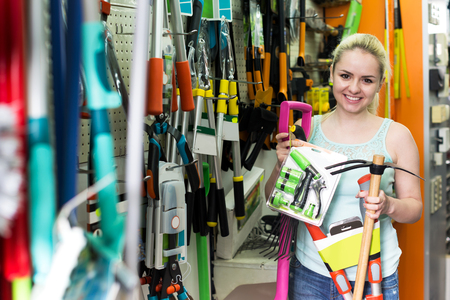 secateur: Cheerful blond woman picking various horticultural sundry in household shop