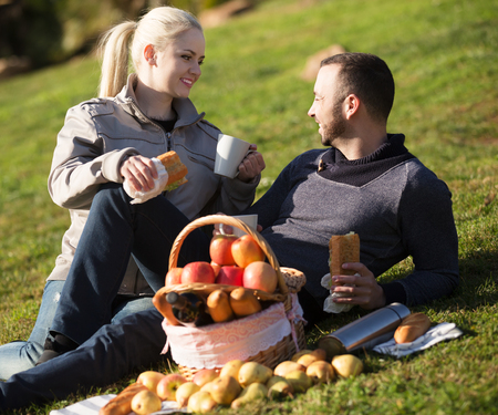 sandwitch: Young smiling family couple lounging in sunny spring day at picnic outdoors. Focus on girl