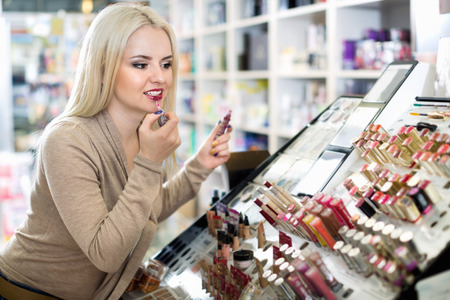 Happy smiling beautiful female customer buying red lipstick in makeup section