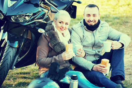 sandwitch: Young smiling couple having picnic with coffee near cycle