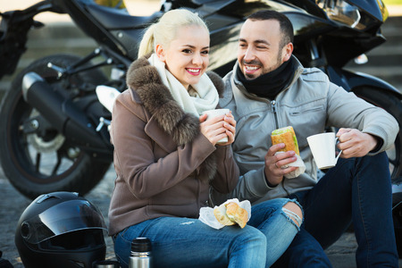 sandwitch: Happy pleasant couple having picnic with coffee near cycle