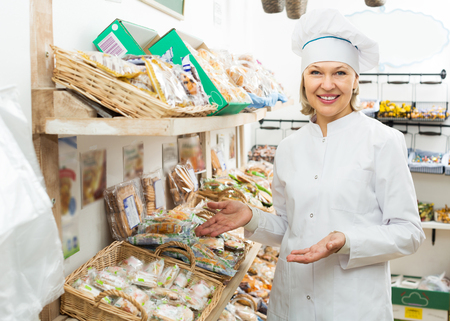 Smiling elderly female offering fresh and tasty pastry in bakery Stock Photo