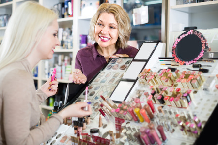 seller: Smiling mature female seller near display with cosmetics in beauty store