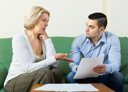 Elderly woman questioning young man about letters from bank at home