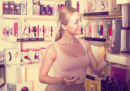 Portrait of adult girl choosing erotic toys in sex shop Stock Photo