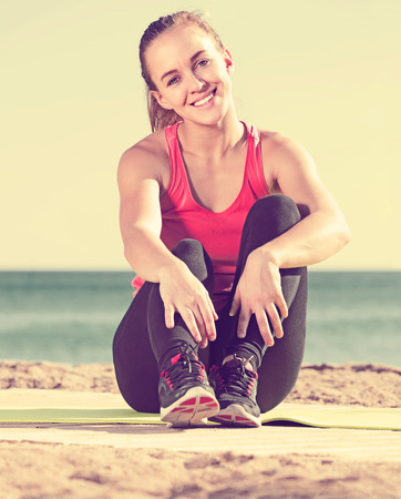 young smiling woman exercising on exercise mat outdoor at the seaside Stock Photo