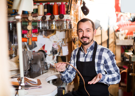 attentiveness: Smiling russian male worker sewing stitches on belt in leather workshop Stock Photo