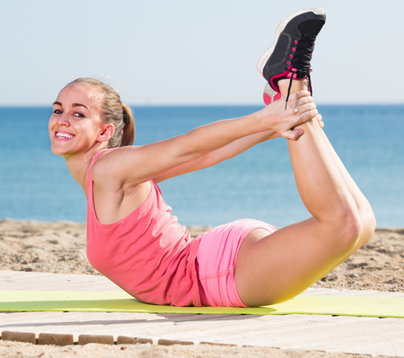 Cheerful young woman working out in beach Stock Photo