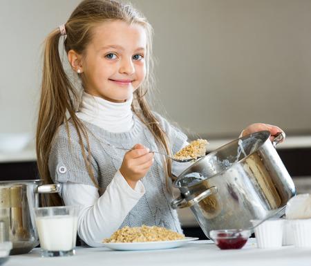 niños desayunando: Small girl cooking oatmeal kasha in home kitchen and smiling Foto de archivo