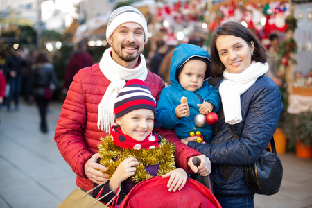 holidays: Cheerful parents with children choosing holidays decorations at Christmas market Stock Photo