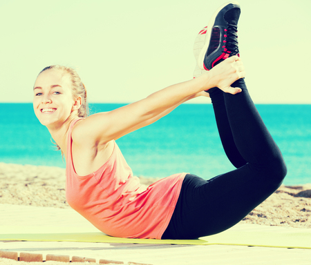 Glad sporty woman exercising at sea beach