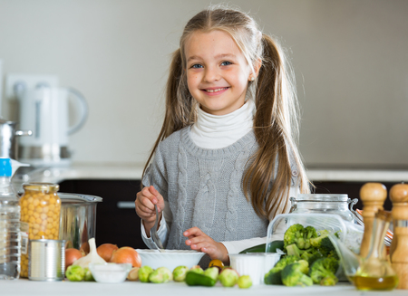 Cute little girl with ponytailes cooking Brussels sprouts in kitchen