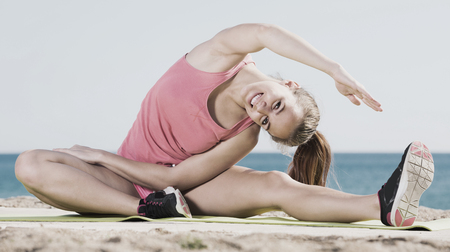 Cheerful young woman in sportswear working out in beach