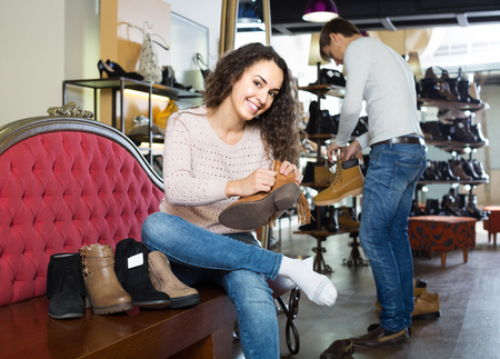 comprando zapatos: smiling european  female buying winter female shoes in  shoe store
