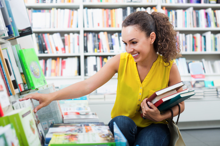 Jonge positieve studente die boeken in harde dekking in boekhandel kiezen Stockfoto