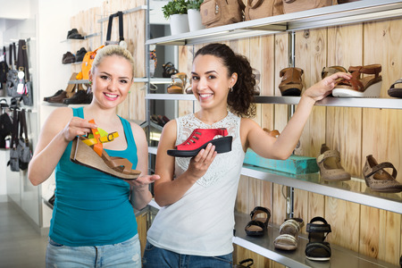 Ttwo glad beautiful young women selecting a shoes and chatting among a shelves. Focus on both persons Stock Photo