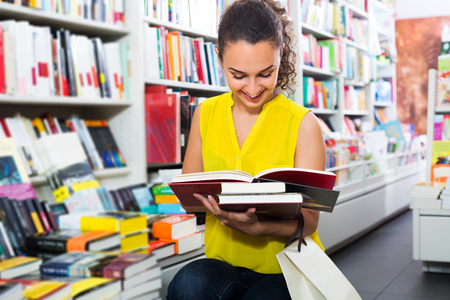 publishers: Brunette woman looking at book in hard cover in bookstore