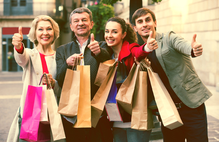 Positive family of four with shopping bags on city street Stock Photo