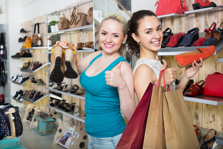 Two happy glad young women shopping the shoes and looking happy with the purchases. Focus on both persons