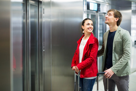 Cheerful young people with luggage standing at metro terminal elevator Stock fotó