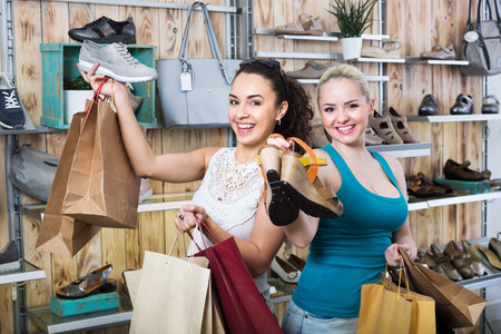 Two glad young women shopping a shoes and looking happy with the purchases. Focus on both persons