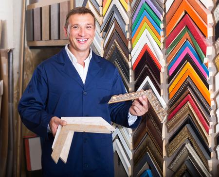 portrait of happy european man in uniform choosing framing moulding in studio