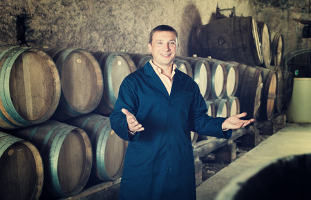 laboratorian: Man professional wine technician working in storage with wooden barrels Stock Photo