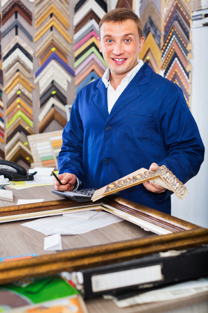 framer: Smiling positive diligent man worker holding picture frame details on counter in studio