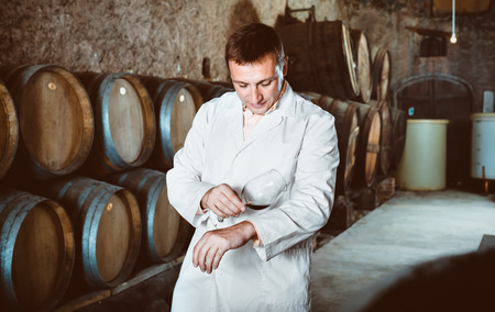 Glad positive  professional taster posing with glass of wine in winery cellar Stock Photo