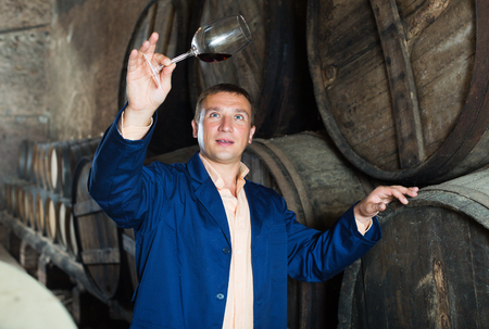 ageing process: Positive young male in robe keeping ageing process of wine under control