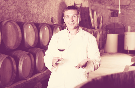 joyful factory sommelier in white robe checking quality of red wine in cellar with barrels