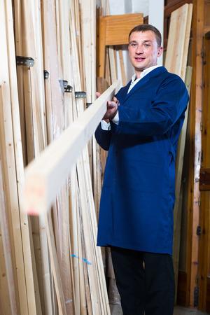 atelier: portrait of happy man in uniform choosing compressed densified wood in picture framing atelier