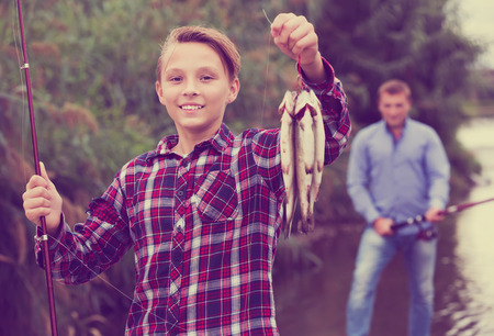 Portrait of smiling teenager boy showing catch fish he holding in hands