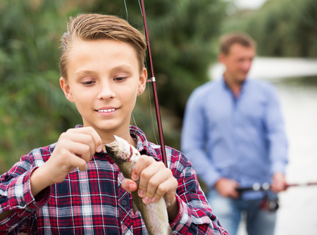 Intrested teenage boy releasing catch on hook fish outdoors Stock Photo