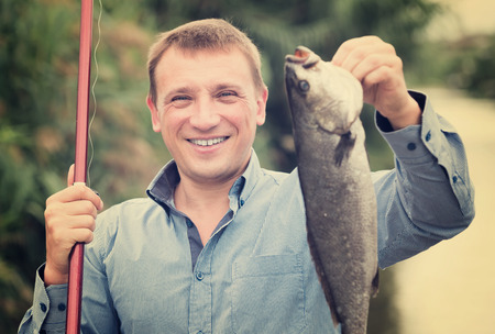 Positive fisherman holding catch freshwater fish in hands Stock Photo